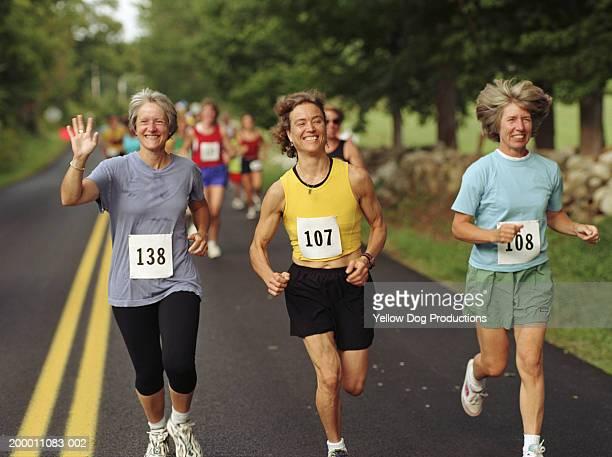 Three happy women running in road race