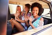 Three Women Sitting In Rear Seat Of Car On Road Trip, Smiling