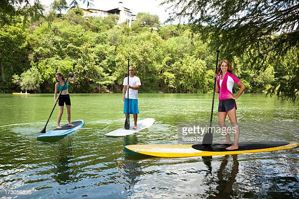 Three happy young adults on paddleboards in Colorado River.