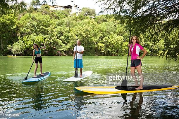Trois heureux jeunes adultes sur des paddleboards du fleuve Colorado.