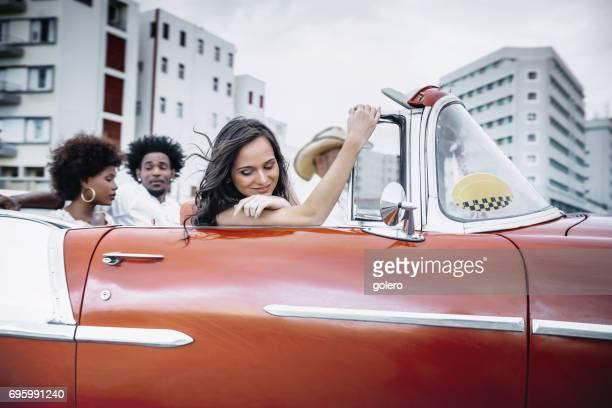 drei glückliche junge Kubaner im Cabrio Oldtimer in Havanna