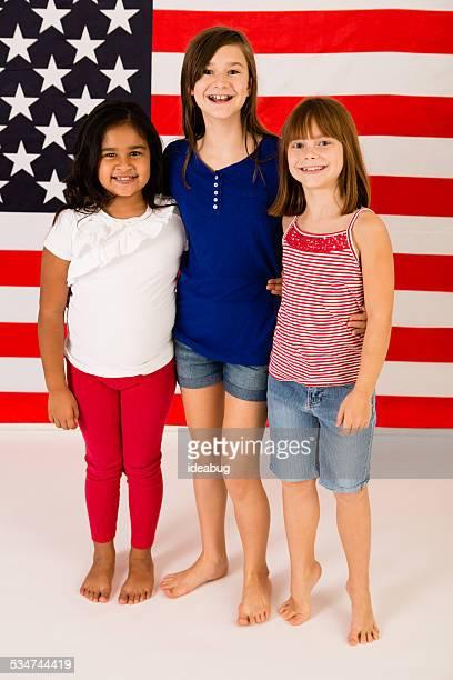 Tre giovani donne felice in piedi davanti alla bandiera americana