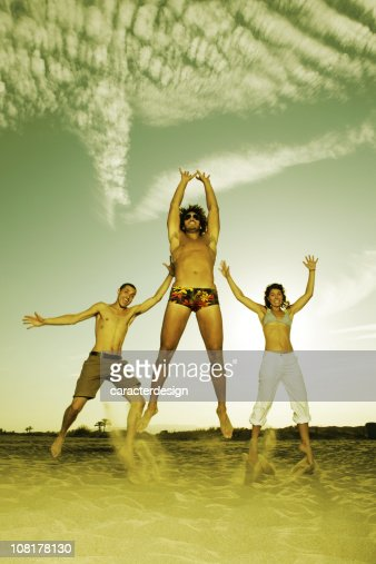 Three Happy Young People Jumping on Beach : Stock Photo