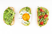 Three healthy toasts with egg, avocado, micro greens and tomatoes. Breakfast or healthy eating concept, plant based food. Flat-lay, top view.