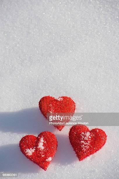 Three heart shaped ornaments on snow