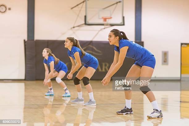 Three high school female volleyball players waiting