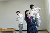 Three high school students practicing stage performance, blurred motion