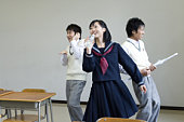 Three high school students practicing stage performance