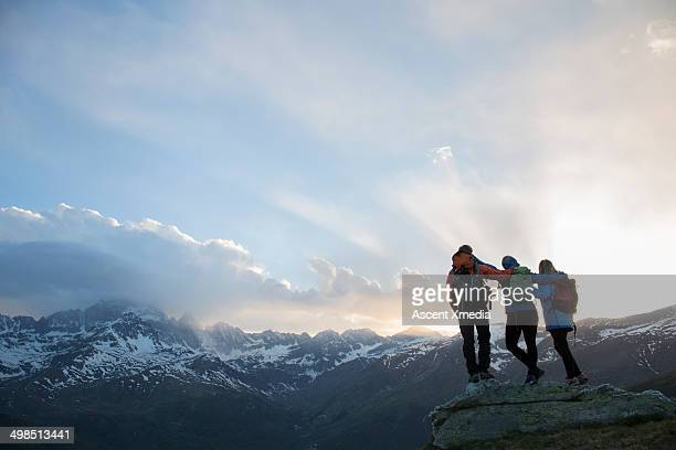 Three hikers link arms on rock above mountains
