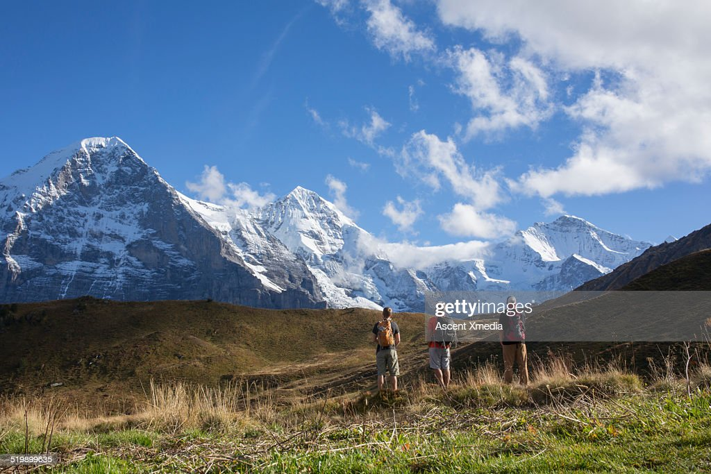 Three hikers stop in mountain meadow, Eiger N Face