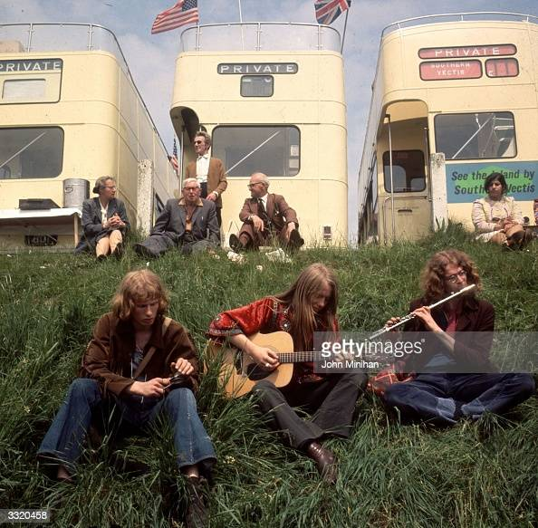 Three hippies playing instruments beside private buses parked on the Epsom Downs on Derby Day