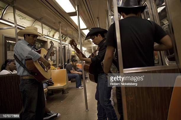 Three Hispanic musicians play guitar and an accordion in a subway car July 9 2010 in Brooklyn New York New York's Metropolitan Transit Authority...