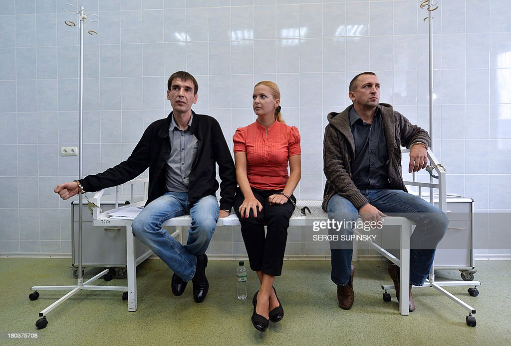 Three HIV-infected patients of the specialized Lavra hospital in Kiev remain handcuffed to the steel frame of a bed as they start an unlimited protest against a government decision to force the closing and relocation of the HIV patients care unit, on September 12, 2013. The three patients and some employees of the unique Ukrainian hospital unit are protesting the Ukrainian government's decision to close the unit and relocate it outside of the city center saying the new location does not fit the standards for proper treatment. Ukraine has one of the fastest growing HIV/AIDS epidemics in the world. AFP PHOTO/ SERGEI SUPINSKY