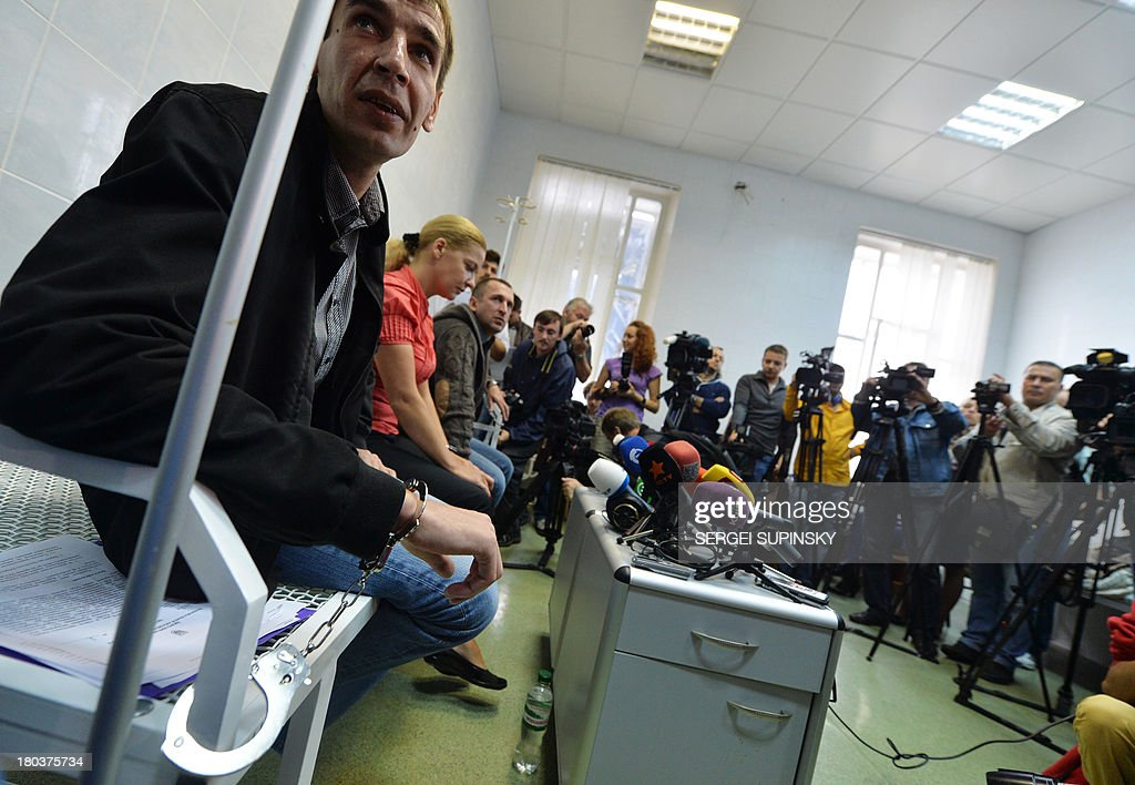 Three HIV-infected patients of the specialized Lavra hospital in Kiev remain handcuffed to the steel frame of a bed as they start an unlimited protest against a government decision to force the closing and relocation of the HIV patients care unit, on September 12, 2013, while journalists film and take photographs. The three patients and some employees of the unique Ukrainian hospital unit are protesting the Ukrainian government's decision to close the unit and relocate it outside of the city center saying the new location does not fit the standards for proper treatment. Ukraine has one of the fastest growing HIV/AIDS epidemics in the world. AFP PHOTO/ SERGEI SUPINSKY