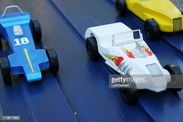 Three homemade wooden toy race cars on a wooden track