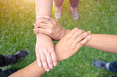 Three human join hands together background, collaboration of business teamwork concept, garden background, Top view.