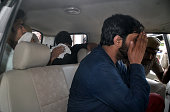 Three Indian men accused of gang raping a woman cover their faces as they sit in a vehicle escorted by a policeman on a visit to a court for a...