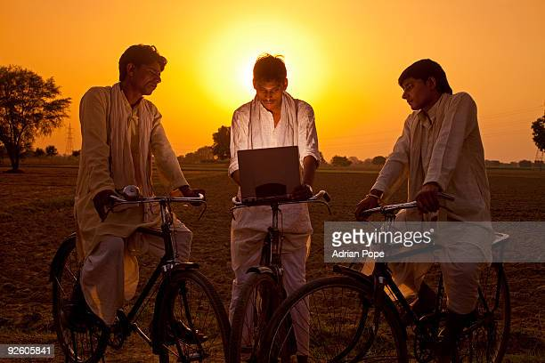 Three Indian men on bicycles looking at laptop