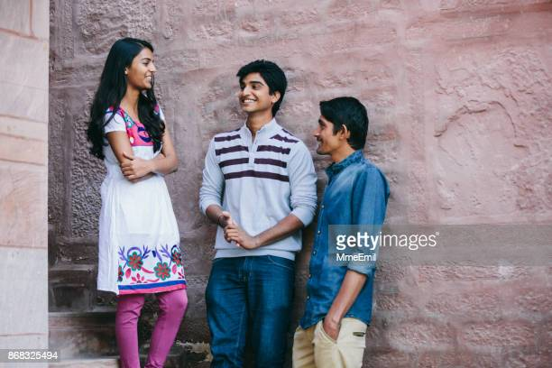 Three Indian millennials leaning on a wall and talking together