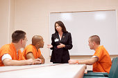 Three inmates listen to a woman discuss options and privileges that they might earn while serving time in prison.