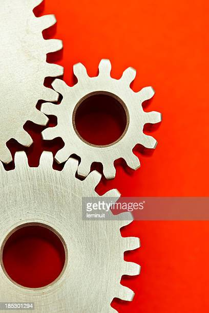 Three interlocking gears on red background