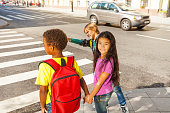 Three international kids stand on street ready to cross the road and holding hands in the city during summer