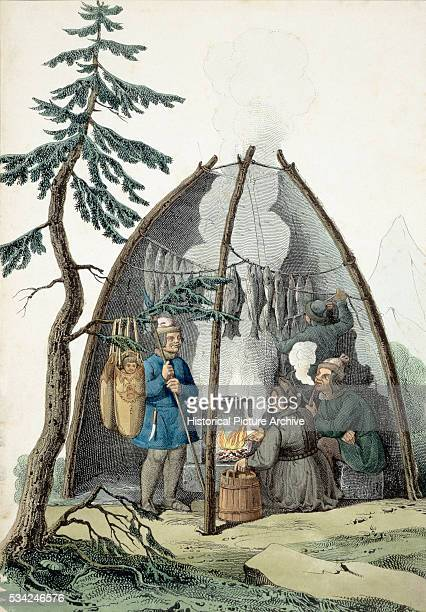 Three Inuits sit inside a tent smoking fish outside two babies hand from the branch of a tree