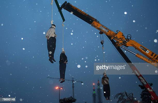 Three Iranian drug traffickers hang limply from the nooses as it snows in a square in central city of Qom 120 kms south of capital Tehran 02 January...