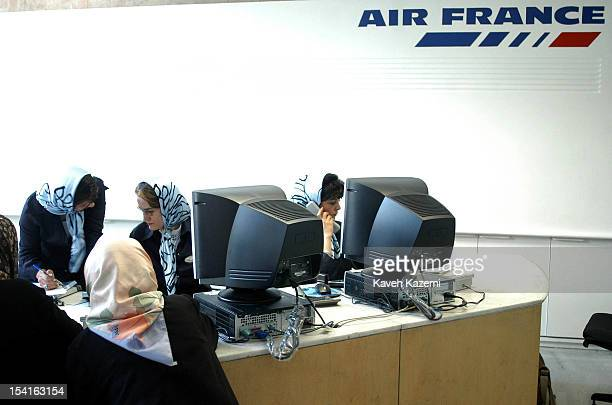 Three Iranian women in headscarves work at the Air France desk after the airline resumed flight operations from Tehran in midJune 2004 after a...
