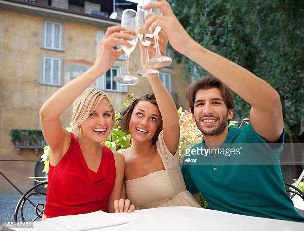 Three Italian friends toasting with you in an outdoor restaurant.