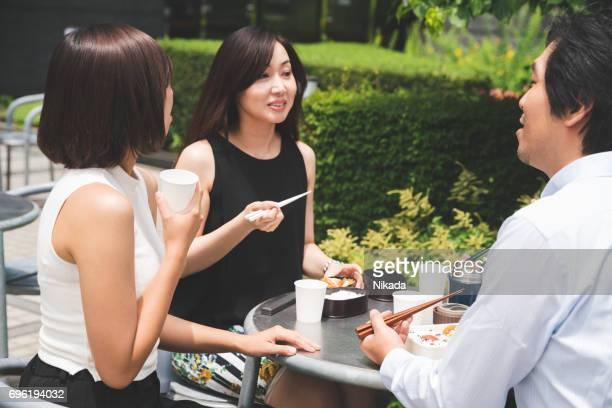 Drei japanischen Büroangestellten, die dem gemeinsamen Mittagessen im freien