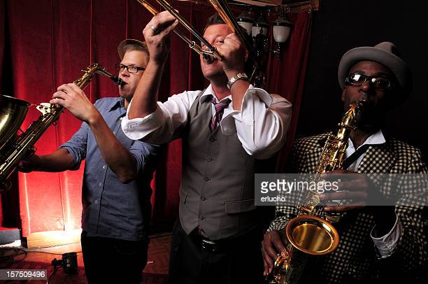 Three jazz musicians playing music with red curtain in back