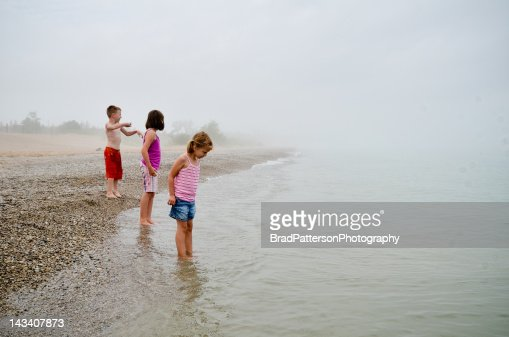 Three kids at lake shore on cloudy day : Stock Photo
