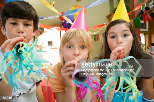 three kids blowing noise makers at a party : Stock Photo