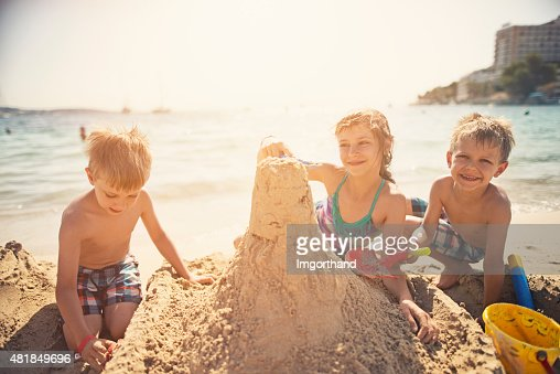 Three kids building a sandcastle