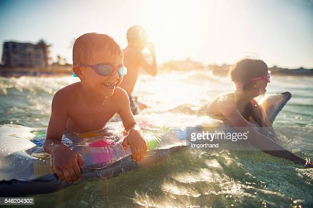 Three kids having fun in sea on air bed