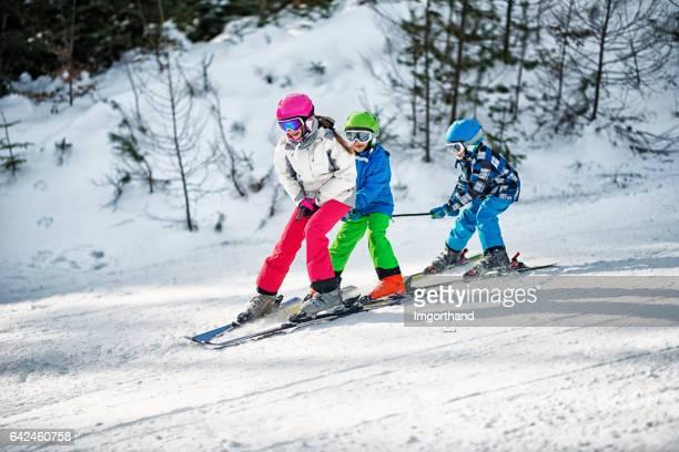 Three kids having fun skiing together on sunny winter day
