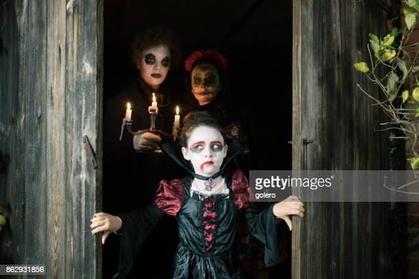 three kids in spooky halloween costumes hiding behind door of barn