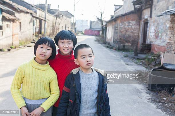 three kids in the chinese old village street