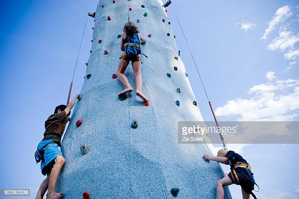 three kids on outdoor climbing wall