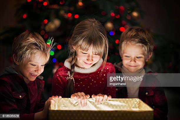 Tre bambini apertura regalo vicino all'albero di Natale