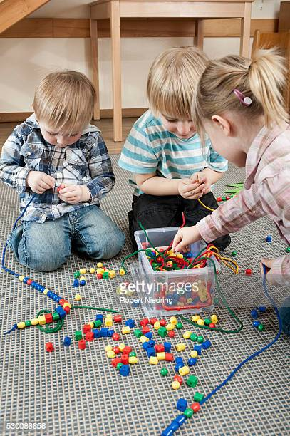 Three kids playing with coloured wooden perls