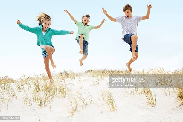 Three kids running and jumping off a sand dune.