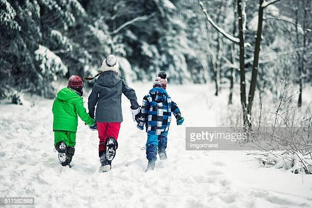 Three kids running in winter forest