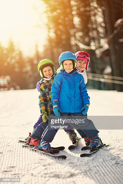 Three kids skiing on sunny winter day