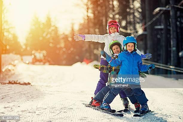 Three kids skiing on sunny winter day