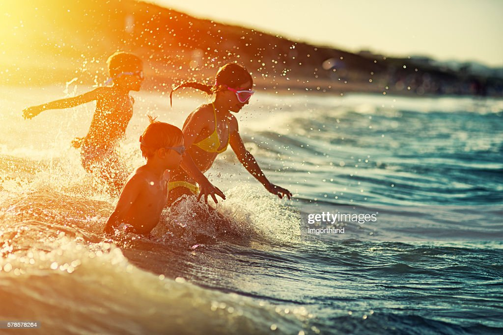 Three kids swimming and having fun at sea at sunset : Stock Photo