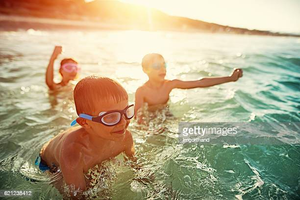 Three kids swimming and having fun in sea