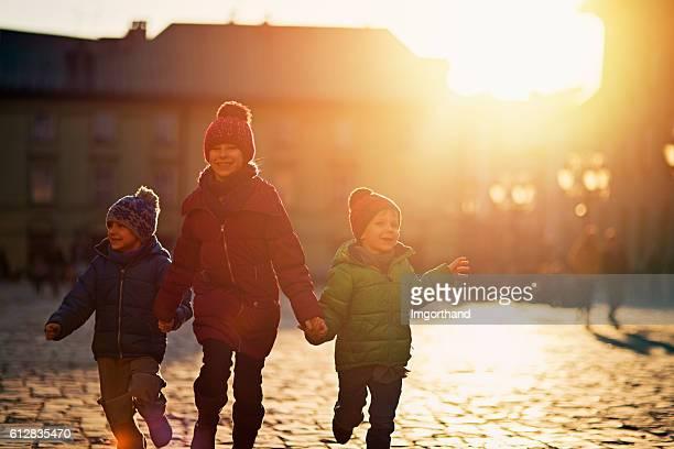 Three kids visiting Krakow old city in autumn
