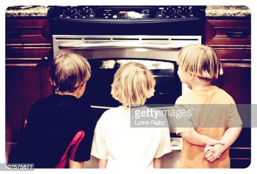 Three kids watching cookies bake